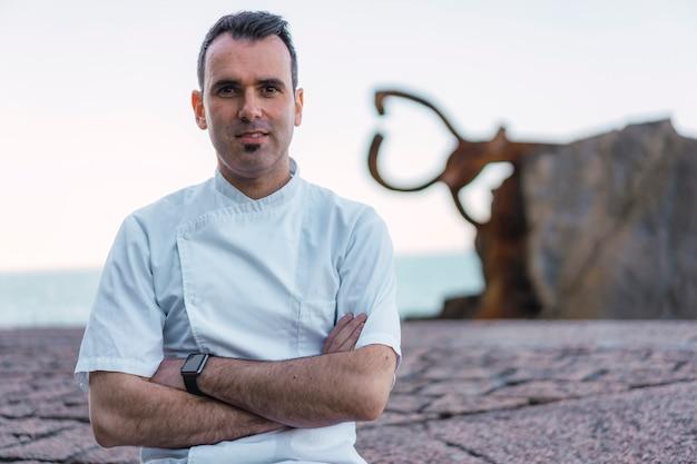 Lebensstil eines kochs, kaukasischer lächelnder koch mit weißer schürze in einem foto an der küste