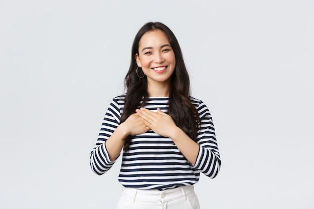 Lebensstil, emotionen der menschen und lässiges konzept. berührte zart lächelnde asiatische frau erhält gerne lob, hält die hände auf dem herzen und grinst dankbar, schätzt kompliment.