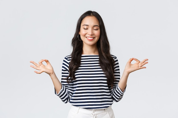 Lebensstil, emotionen der menschen und lässiges konzept. ruhige, glückliche junge frau, die sich während der meditation friedlich fühlt, die augen schließen und lächeln, während sie die hände in der zen-nirvana-geste hält, macht yoga-übungen