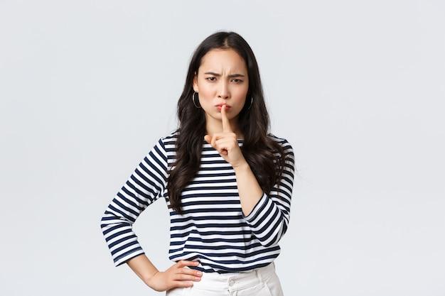 Lebensstil, emotionen der menschen und lässiges konzept. wütende ernsthafte junge asiatische frau, die laut ist, schimpft mit wütendem gesicht und zeigefinger auf die lippen, sagt, sei ruhig