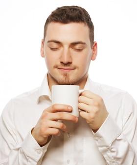 Lebensstil, essen und leute konzept: lässiger junger mann, der weiße tasse mit kaffee oder tee hält.