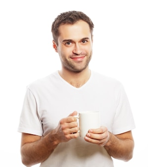 Lebensstil, essen und menschenkonzept: lässiger junger mann, der weiße tasse mit kaffee oder tee hält.