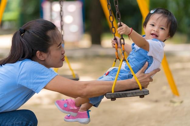 Lebensstil-familie, glückliche mutter und tochter, die zeit auf dem spielplatz im park genießt