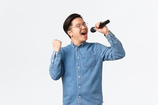 Lebensstil, freizeit und menschenkonzept. sorgloser glücklicher asiatischer mann, der genießt, beim karaoke zu singen, mikrofon und faustpumpe im entzücken hält und über weißer wand auftritt