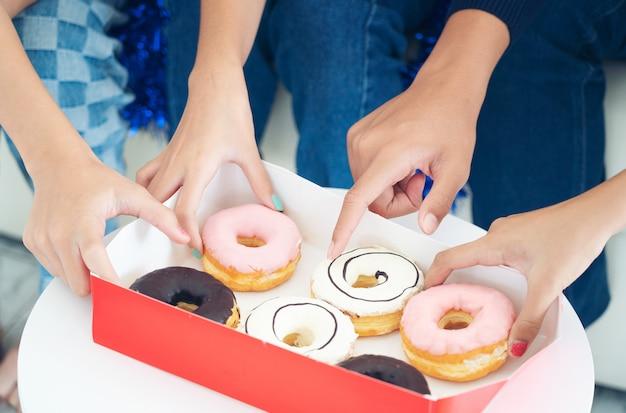 Lebensstil-freund haben spaß mit donut, die gruppe hände, die halten, versüßen donutnachtisch, freundschaft, friedenskonzept.