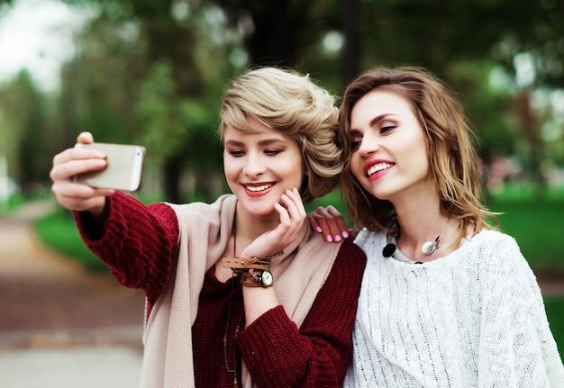 Lebensstil, glück, emotion und menschenkonzept: freunde machen selfie. zwei schöne junge frauen machen selfie im herbstpark.