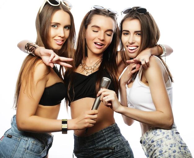 Lebensstil, glück, emotion und menschenkonzept: gruppe junger frauen, die spaß beim karaoke haben