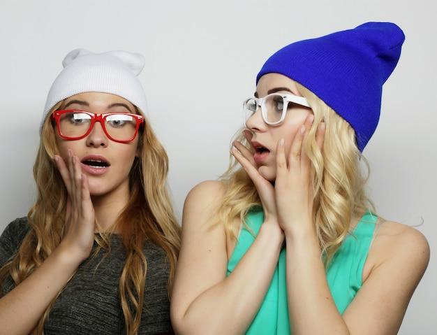 Lebensstil, glück, emotion und menschenkonzept: nahaufnahme des mode-lifestyle-porträts von zwei jungen hipster-mädchen besten freunden, die helles make-up und ähnliche trendige hüte tragen und lustige gesichter machen.