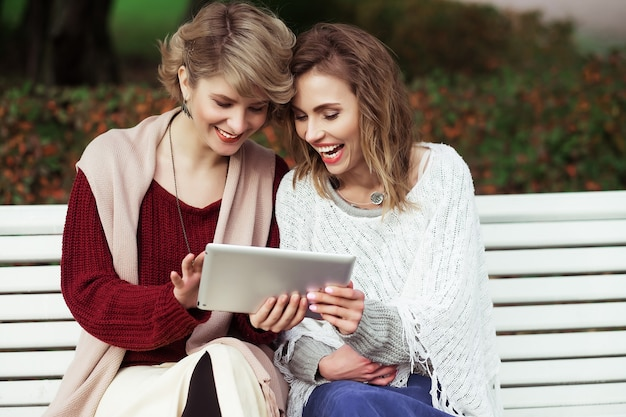 Lebensstil, glück, emotion und menschenkonzept: schöne frauen mädchen herbst mit tablet im freien