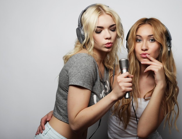 Lebensstil, glück, emotion und menschenkonzept: schönheits-hipster-mädchen mit einem mikrofon, die singen und spaß haben