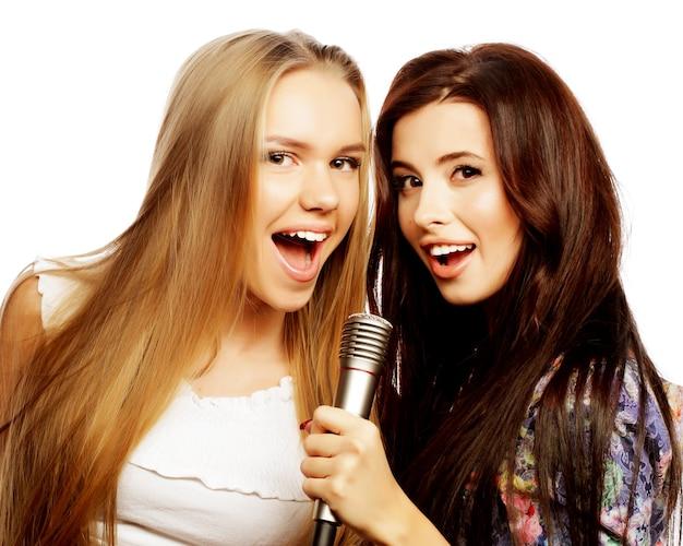 Lebensstil, glück, emotion und menschenkonzept: zwei schönheits-hipster-mädchen mit einem mikrofon, die singen und spaß haben