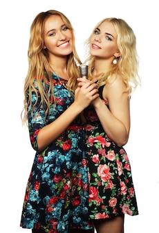 Lebensstil, glück, emotion und menschenkonzept: zwei schönheitsmädchen mit einem mikrofon, die singen und spaß haben