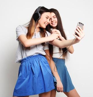 Lebensstil, glück, emotionalität und menschenkonzept. schönheit hipster mädchen mit einem mikrofon singen und fotografieren mit smartphone auf weiß