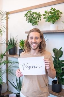 Lebensstil. gut aussehender junger bärtiger mann, der drinnen mit zimmerpflanzen steht, die veganes plakat in der guten stimmung halten