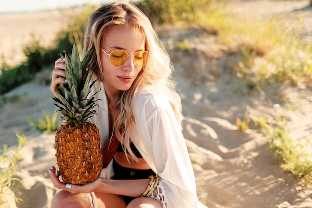 Lebensstil im freienbild der lachenden hübschen frau mit saftiger ananas, die am sonnigen strand entspannt. trendiges sommeroutfit