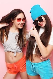 Lebensstil, leute, teenager und freundschaftskonzept - glücklich lächelnde hübsche teenager-mädchen oder freunde, die über rosa hintergrund umarmen