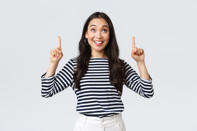 Lebensstil, menschen emotionen konzept. aufgeregtes, gut aussehendes asiatisches mädchen, das erfreut lächelt, als es ein ausgezeichnetes produkt gefunden hat, mit dem finger auf die werbung zeigt und zufrieden aussieht, empfehlen sie die promo