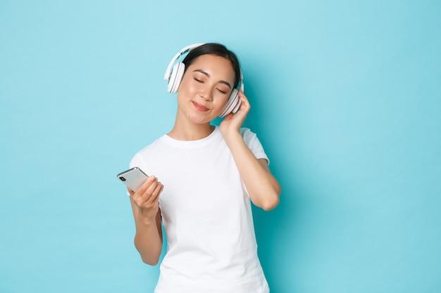 Lebensstil, menschen und freizeitkonzept. verträumte schöne asiatische mädchen schließen augen und lächeln, genießen, musik in drahtlosen kopfhörern zu hören, zur melodie zu tanzen, smartphone zu halten, blaue wand