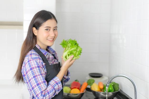 Lebensstil schöne asiatische gesunde mädchenfülle glücklich, waschendes gemüse in der spülbecken