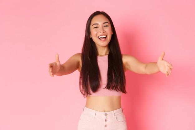 Lebensstil, schönheit und frauenkonzept. porträt des freundlichen fröhlichen hübschen asiatischen mädchens, das hände für umarmung ausstreckt, arme zum kuscheln ausstreckt, in herzlichem willkommen umarmt, jemanden begrüßt, rosa wand.