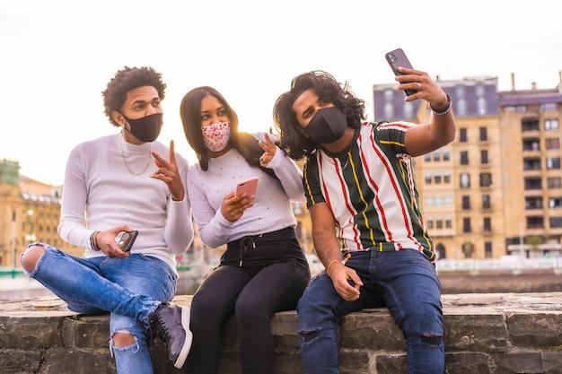 Lebensstil, selfie von drei freunden auf der straße mit gesichtsmasken.