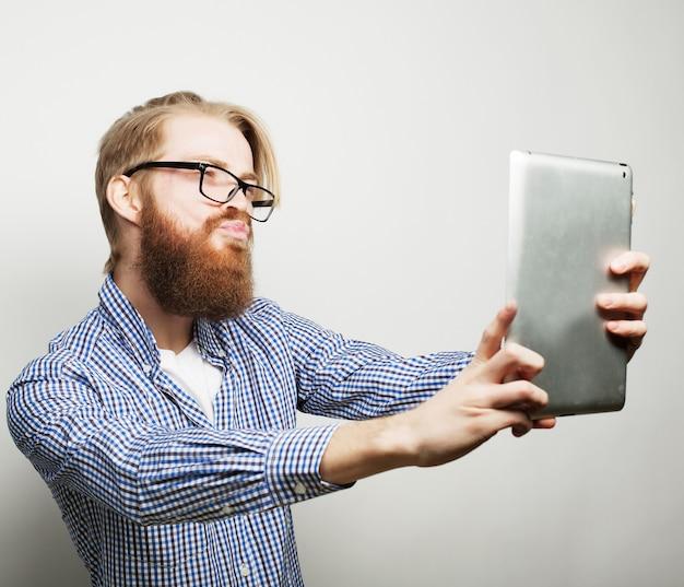 Lebensstil, technik und menschenkonzept: glückliches selfie. junger bärtiger mann, der ein tablet hält und ein foto von sich macht, während er vor weißem hintergrund steht
