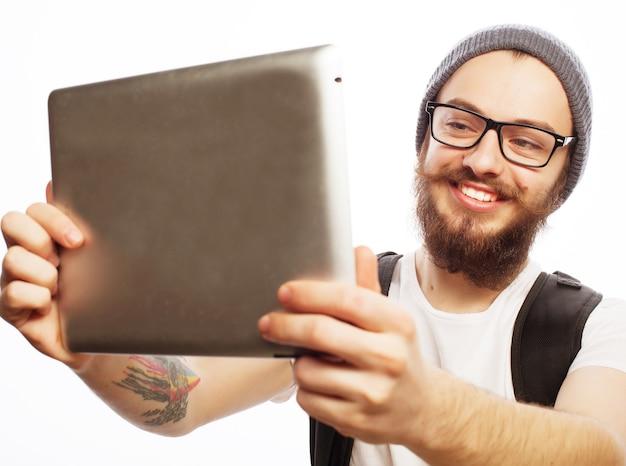 Lebensstil, technologie und menschenkonzept: glückliches selfie. junger bärtiger mann, der ein tablet hält und ein foto von sich macht, während er vor weißem hintergrund steht