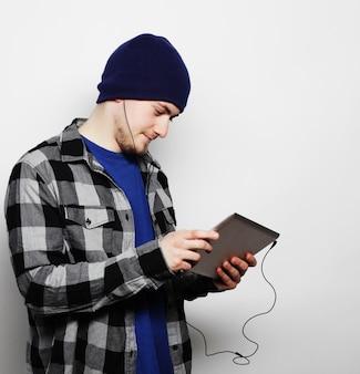 Lebensstil, technologie und menschenkonzept: hübscher junger mann mit hemd und hut, der an einem digitalen tablet arbeitet und lächelt, während er auf grauem hintergrund steht