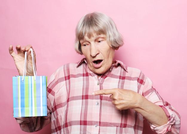 Lebensstil und leutekonzept der glücklichen älteren frau mit einkaufstasche über rosa
