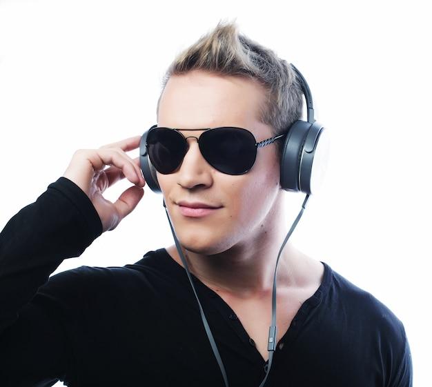 Lebensstil und menschenkonzept: glücklicher junger mann, der mit kopfhörern musik hört