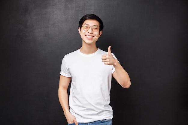Lebensstil und menschenkonzept. hübscher junger asiatischer mann im weißen t-shirt, sonnenbrille, die über zeigt, zeigt daumen hoch und nickt zustimmend, lächelt zufrieden, hinterlässt positives feedback