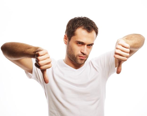 Lebensstil und menschenkonzept: junger zufälliger mann, der die daumen nach unten negatives handzeichen auf weißem hintergrund macht