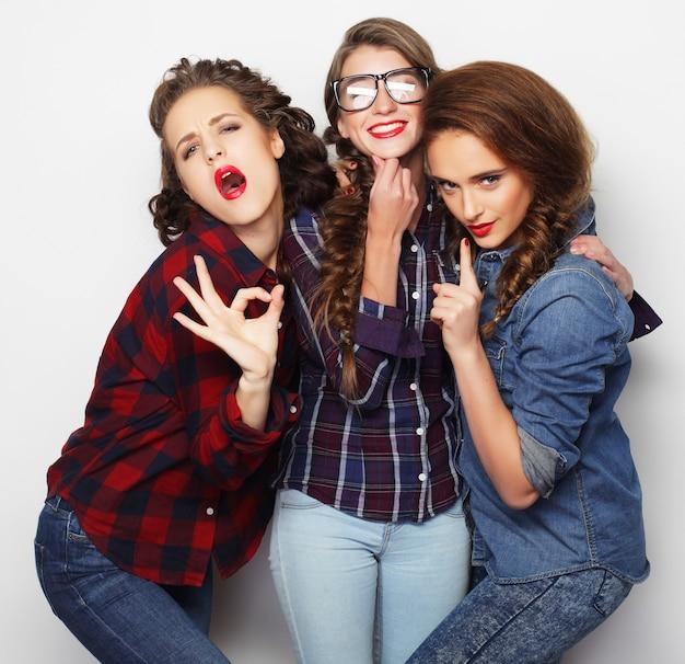 Lebensstil- und personenkonzept: modeporträt von drei stilvollen besten freundinnen der sexy mädchen, über weißem hintergrund. glückliche zeit zum spaß.