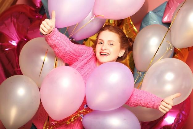 Lebensstil- und personenkonzept: porträt der glücklichen lächelnden jungen frau, die okay geste zeigt, über hintergrund von luftballons.