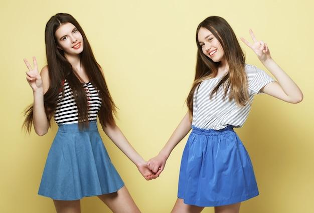 Lebensstil- und personenkonzept: zwei junge freundinnen stehen zusammen und haben spaß. blick auf die kamera. gelber hintergrund.