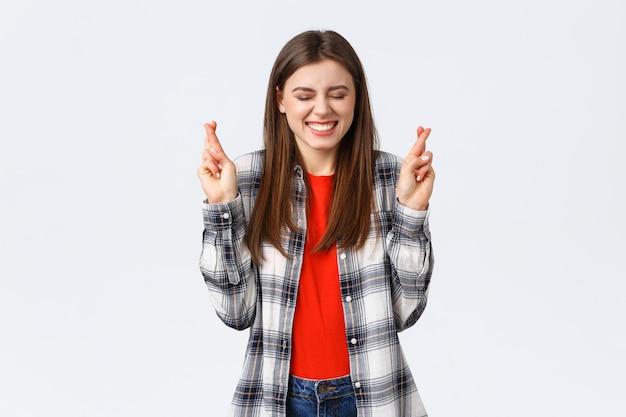 Lebensstil, verschiedene emotionen, freizeitkonzept. aufgeregtes, glückliches junges mädchen, das sicher ist, dass der traum wahr wird, die augen schließen und optimistisch lächeln, als kreuzfinger viel glück, wünsche machen oder beten