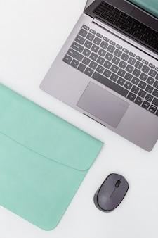 Lebensstilarbeitsplatz für studenten, büroangestellte, freiberufler. modernes bildungskonzept. grauer laptop im blauen kasten und in der drahtlosen maus. ansicht von oben. flach liegen.