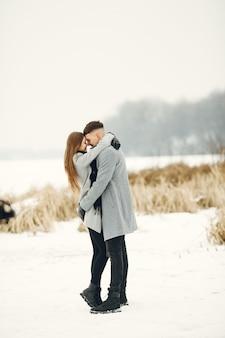 Lebensstilaufnahme des paares, das im verschneiten wald geht. menschen verbringen winterferien im freien.