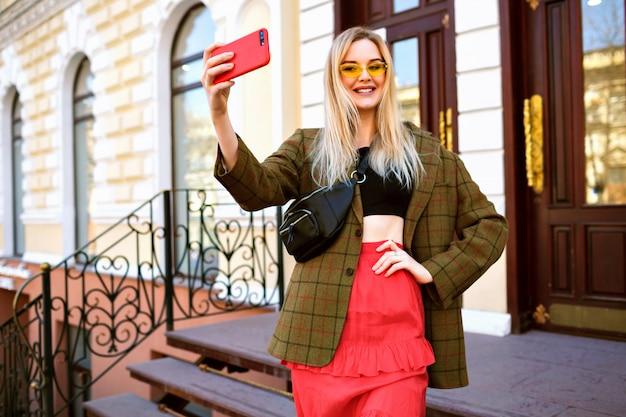 Lebensstilbild der hübschen stilvollen eleganten blondine, die selfie auf der straße macht,