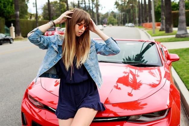 Lebensstilbild der reisefrau, die auf der motorhaube des erstaunlichen roten cabrio-sportwagens sitzt. straßen von los angeles