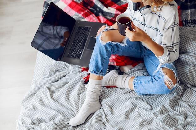 Lebensstilbild, frau, die kaffee trinkt und computer benutzt, warme socken und trendige jeans tragend. auf dem bett sitzen. früher morgen. draufsicht.