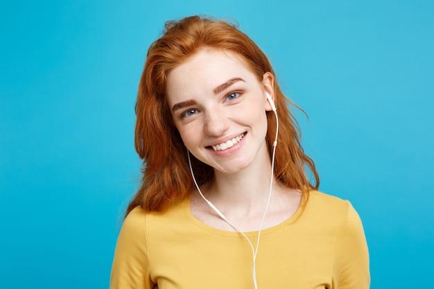 Lebensstilkonzeptporträt des fröhlichen glücklichen roten haarmädchens des ingwers genießen das hören von musik mit freudigem lächeln der kopfhörer lokalisiert auf blauem pastellwandkopierraum