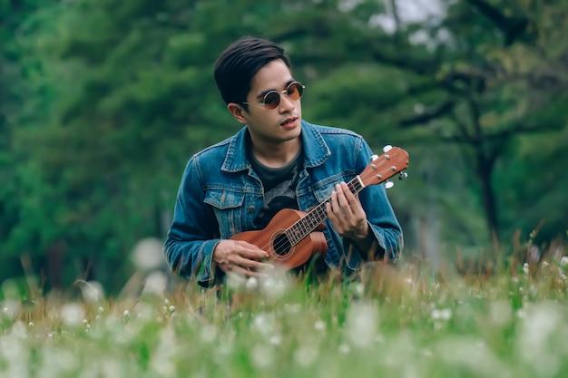 Lebensstilmann, der im park mit seinem ukulelenweinleseton sich entspannt