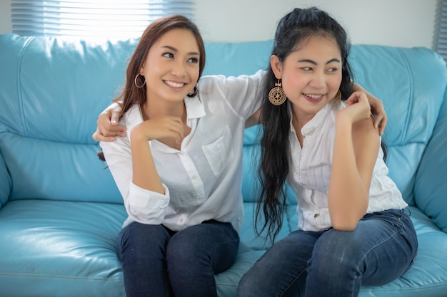 Lebensstilporträt asiatinnen von besten freunden - lächeln glücklich auf sofa am wohnzimmer