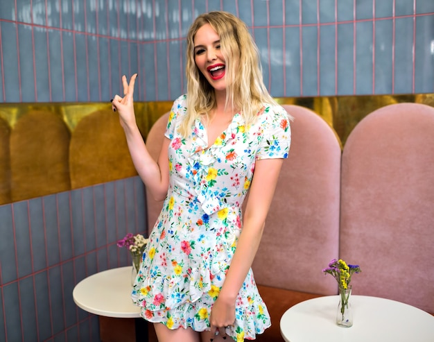 Lebensstilporträt der hübschen lustigen blonden hipsterfrau, die am stilvollen restaurant aufwirft, mini-blumenkleid trägt, lächelnd zwinkert und v wissenschaft durch ihre hände zeigt, positive stimmung.