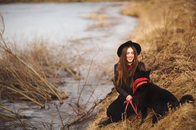 Lebensstilporträt der jungen frau im schwarzen hut mit ihrem hund