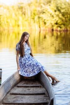Lebensstilporträt der jungen schönheit sitzend am motorboot. mädchen, das spaß am boot auf dem wasser hat. das mädchen sitzt auf einem boot in einem see