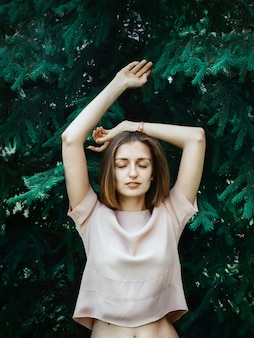 Lebensstilporträt der jungen weißen frau mit den kurzen haaren, die vor kiefer mit den augen geschlossen und die hände angehoben stehen