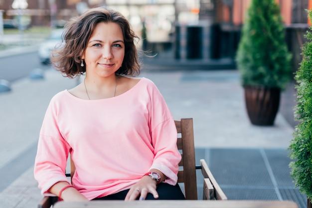 Lebensstilporträt der lächelnden jungen kaukasischen frau, die im straßencafé sitzt.
