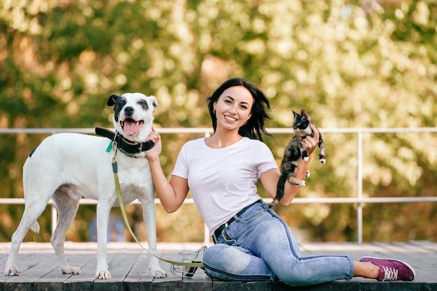 Lebensstilporträt der schönen brünetten frau mit der kleinen katze und dem großen hund, die draußen im park sitzen.